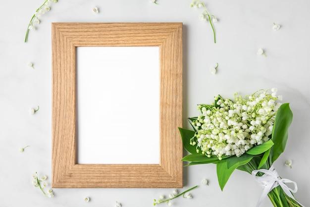 Cadre photo vierge avec bouquet de fleurs de muguet sur blanc. pose à plat. vue de dessus