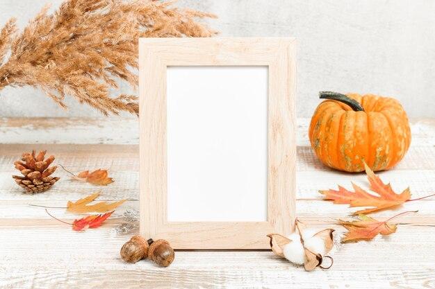 Cadre photo vierge avec des décorations de citrouille et d'automne