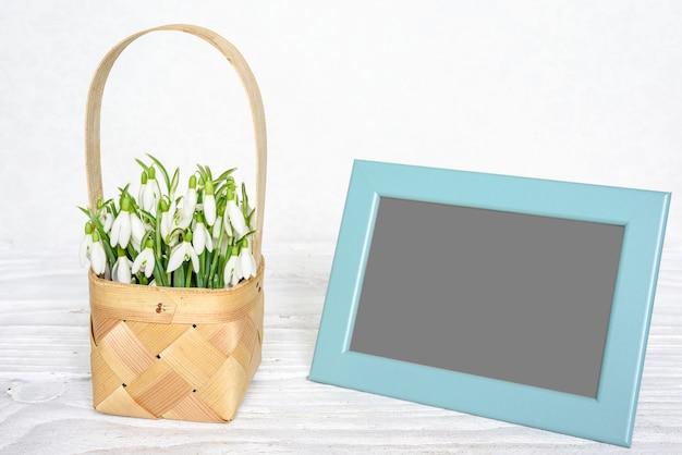 Cadre photo vierge avec des fleurs de perce-neige au printemps dans un panier en osier sur une table en bois blanc