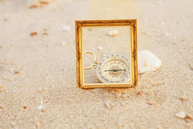Cadre photo vintage en or sur la plage de sable.