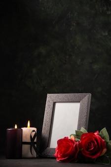 Cadre photo vue de face avec des fleurs rouges et des bougies sur le sol sombre guerre mort funéraire mal