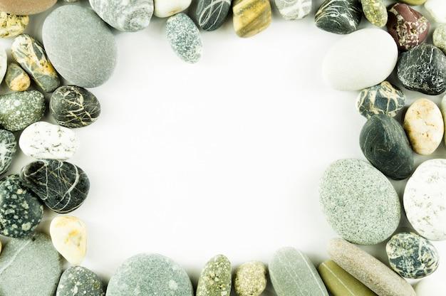 Cadre de pierres de la mer sur fond blanc