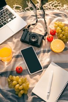Cadre de pique-nique sur une table extérieure avec fruits frais, ordinateur portable, téléphone, appareil photo