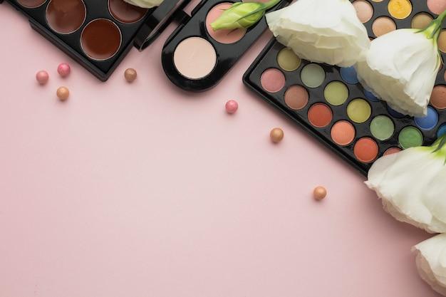 Cadre plat avec fleurs et palettes de maquillage
