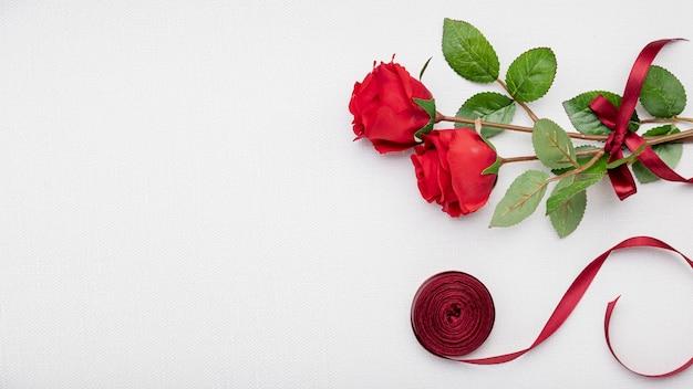 Cadre plat avec roses et ruban rouge
