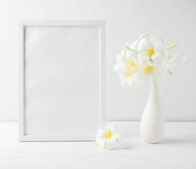 Cadre de portrait maquette et belle fleur de spa frangipani dans un vase blanc en céramique moderne sur fond de mur blanc de table en bois, nature morte aux tons doux