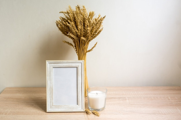 Cadre de portrait mock up avec des fleurs séchées sur une table en bois. photo de haute qualité