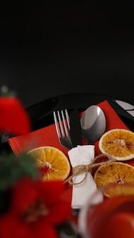 Cadre pour le dîner de noël festif sur table noire avec décoration du nouvel an et oranges sèches