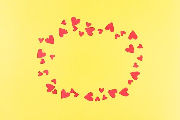 Cadre pour les inscriptions de la découpe rouge et des coeurs en papier sur un fond jaune salutation