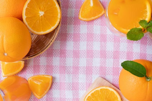 Cadre pour texte avec des fruits orange en tranches sur fond de texture de nappe rose, vue de la table ci-dessus.