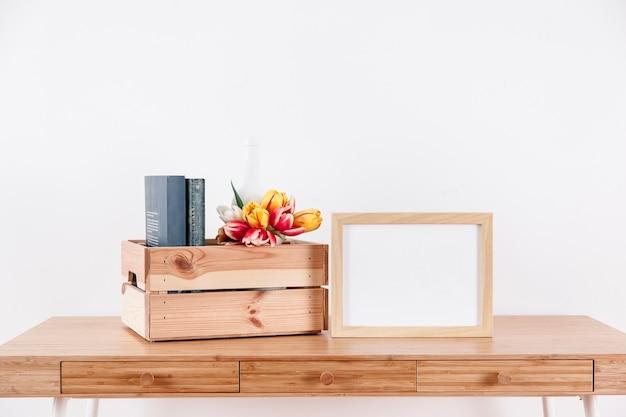 Cadre près de la boîte avec des fleurs et des livres