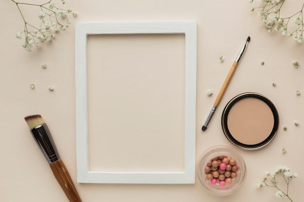 Cadre avec produits de maquillage à côté