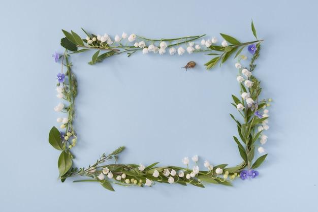 Cadre rectangulaire floral avec espace de copie sur une surface bleue