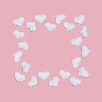 Cadre romantique de coeurs blancs sur fond rose de vacances pour la saint valentin. concept d'amour.