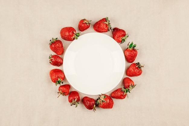 Cadre rond aux fraises et assiette blanche vide