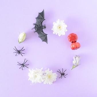 Cadre rond composé d'articles d'halloween, de chauves-souris, d'araignées, de fleurs et de citrouilles sur fond violet.