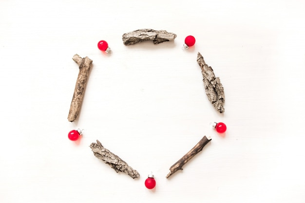 Cadre rond en écorce, cônes de sapin et boules rouges. composition de laïque plat de noël d'hiver