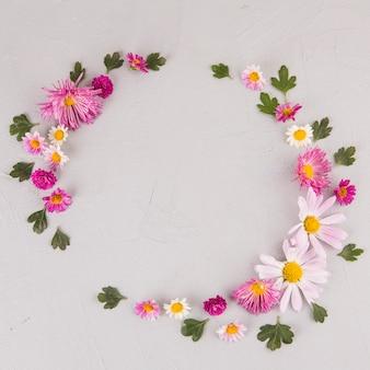 Cadre rond de fleurs et feuilles sur table