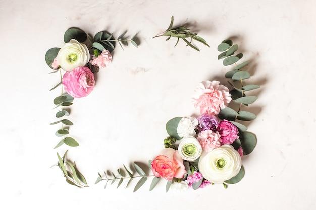 Cadre rond floral avec branches et feuilles d'eucalyptus, fleurs plates, vue de dessus avec espace de copie