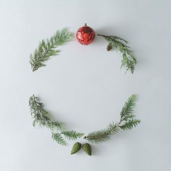 Cadre rond de noël fait avec des branches d'arbres à feuilles persistantes d'hiver naturelles et une décoration de boule rouge. couronne plate.