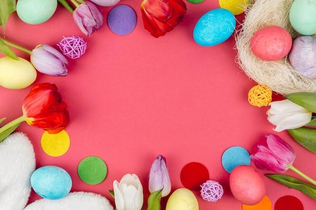 Cadre rond d'oeufs de pâques et de tulipes sur table