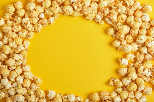 Cadre rond de pop-corn sur fond jaune vue de dessus de l'espace de copie