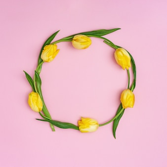 Cadre rond de tulits en fleurs jaunes sur rose. motif de fleurs de printemps