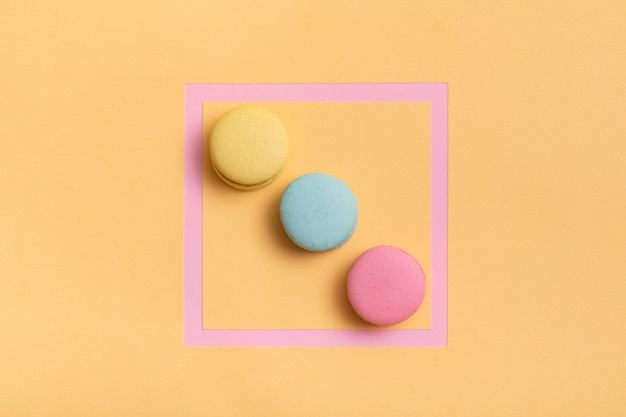 Cadre rose avec des macarons colorés
