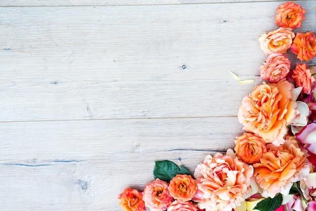 Cadre de roses sur fond en bois gris.