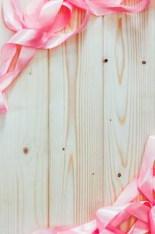 Cadre de rubans roses sur fond en bois naturel