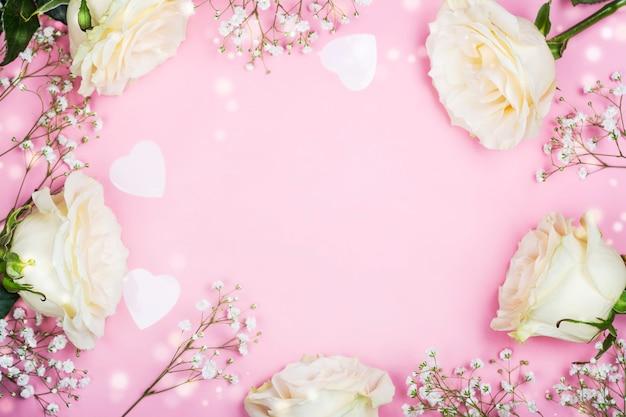 Cadre saint valentin avec des fleurs blanches sur rose