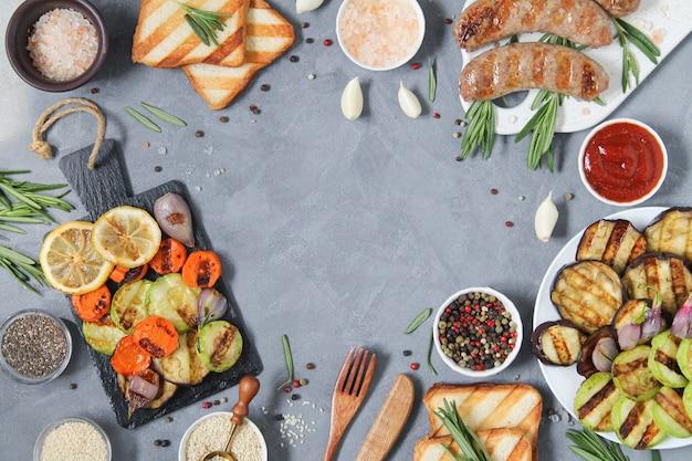 Cadre de saucisses grillées, légumes grillés, pain, salade, différentes collations, épices et herbes vue de dessus