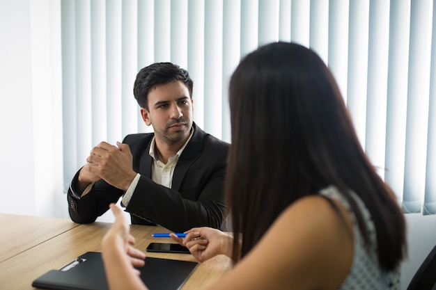 Cadre sérieux écoutant une partenaire ou une employée