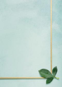 Cadre simpliste avec des feuilles d'oeillets sur une surface bleue
