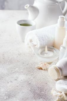 Cadre de soins du visage cosmétiques blanc avec service à thé sur pierre claire