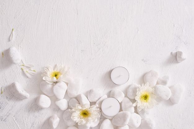Cadre spa avec fleur blanche, bougie sur table en pierre