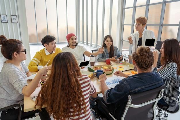 Cadre supérieur asiatique présentant les idées créatives devant le groupe multiethnique