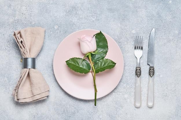 Cadre de table élégance avec plaque rose décorée de fleurs roses sur fond gris. dîner de vacances d'élégance. vue de dessus. espace pour le texte.