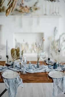 Cadre de table élégant avec des fleurs séchées. assiette avec fourchette et couteau doré vintage, bougies, serviettes bleu poussiéreux sur table en bois. décoration de mariage d'hiver.