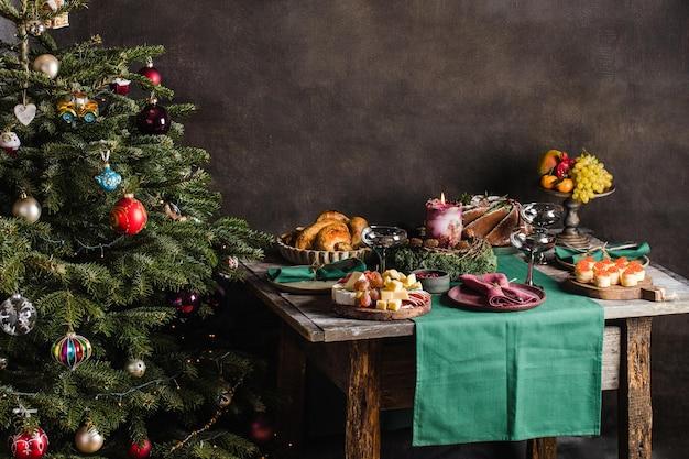 Cadre de table élégant pour le dîner de noël en famille avec sapin de noël en arrière-plan et cadeaux sur...
