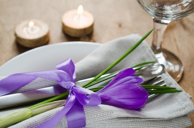 Cadre de table avec fleurs fraîches et bougies.