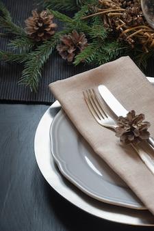 Cadre de table de noël avec argenterie et décor à feuilles persistantes naturel foncé.