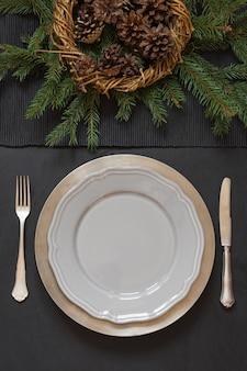 Cadre de table de noël avec couverts et décor à feuilles persistantes sombres.