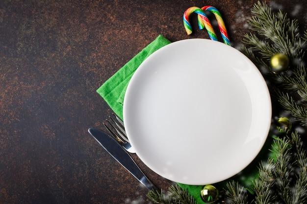 Cadre de table de noël avec des décorations de fête sur une nappe blanche sur fond noir