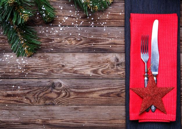 Cadre de table de noël avec fourchette et couteau, étoile rouge décorée et serviette de table rouge