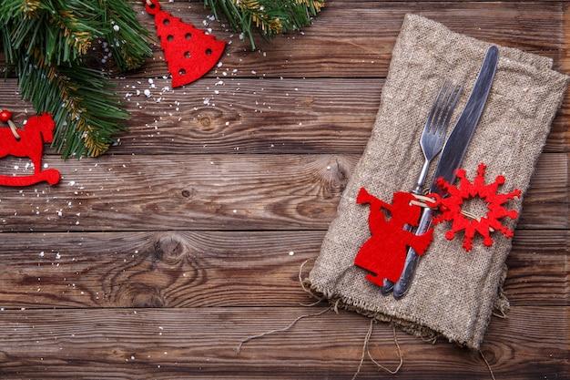 Cadre de table de noël avec fourchette et couteau, jouets de noël rouges décorés