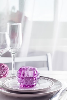 Cadre de table de noël violet avec chandelier et verres de vin