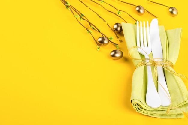 Cadre de table de pâques avec des couverts de cuisine sur un fond jaune vif