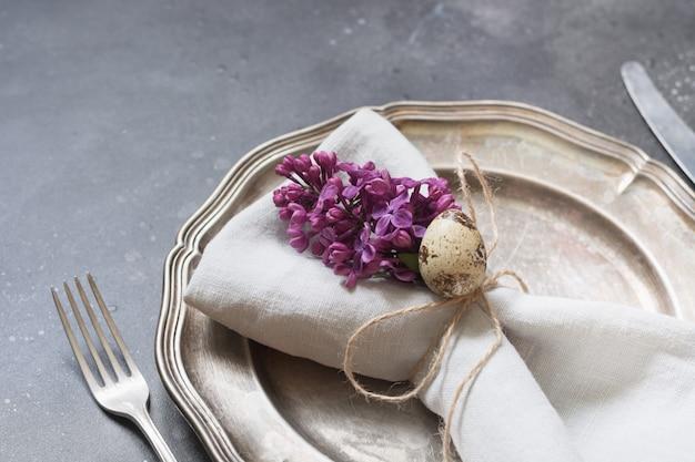 Cadre de table de pâques avec des fleurs lilas sur noir.