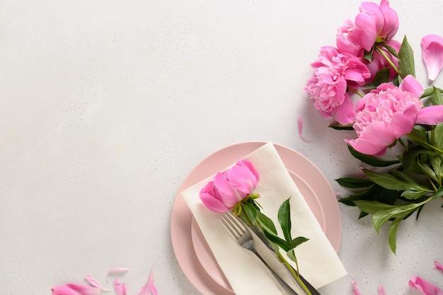 Cadre de table romantique de printemps avec des fleurs de pivoine rose sur un tableau blanc.